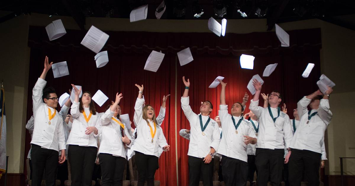 Culinary Institute of America students celebrating graduating with their culinary arts degrees.