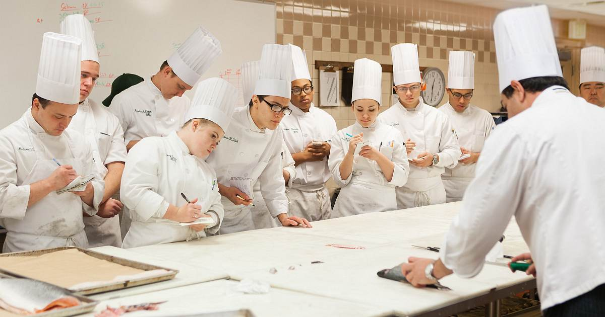 Is culinary school worth it? Students in a CIA classroom learning from an instructor.