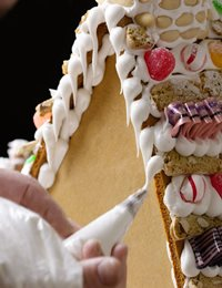 Photo image of royal icing being applied to a gingerbread house.