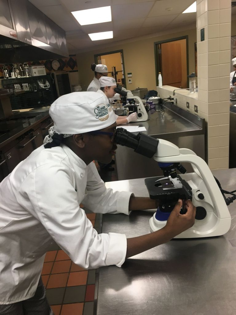 Culinary Science student Majestic Bryant-Lewis studying agar under microscope